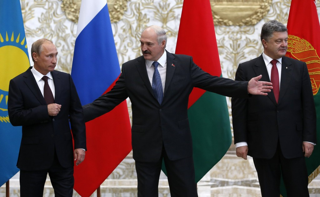 Russia's President Putin, Belarus' President Lukashenko and Ukraine's President Poroshenko react while posing for a family photo during their meeting in Minsk